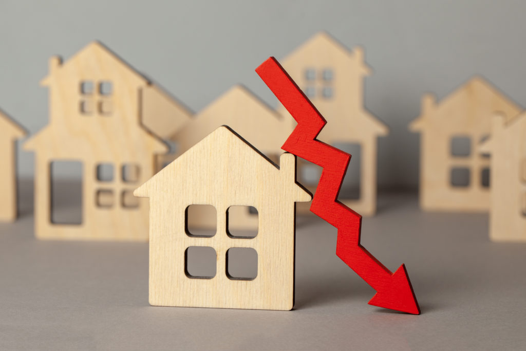 Arrow down and many houses. Falling real estate prices market. Buying and selling house.
